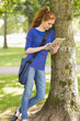 Happy student leaning against a tree using her tablet pc
