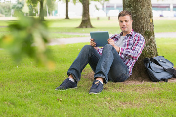 Happy student using his tablet pc outside leaning on tree
