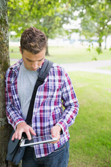 Handsome student leaning on tree using his tablet