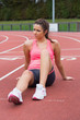Young sporty woman sitting on the running track