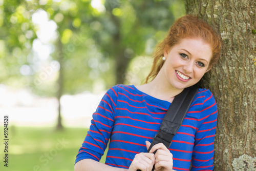 Cheerful redhead student leaning against a tree