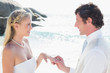 Man placing ring on pretty blonde brides finger