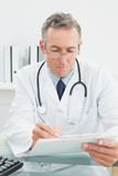 Doctor writing a report at desk in medical office