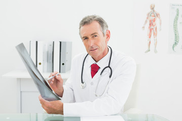 Confident doctor with x-ray picture of lungs in office