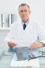 Confident male doctor sitting in office