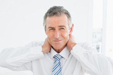Portrait of a mature man suffering from neck pain