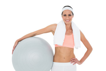 Portrait of a smiling fit woman holding fitness ball