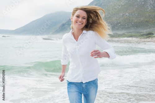 Portrait of a smiling woman running at beach
