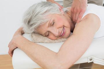 Physiotherapist massaging a senior woman's shoulder