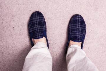 Feet wearing slippers on carpet