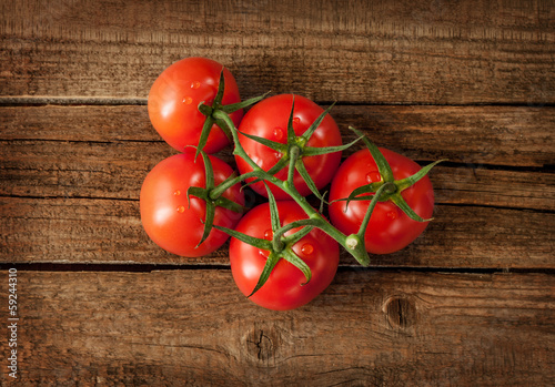 Fresh wet tomato branch on vintage wood table