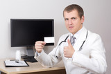 young male doctor showing business card and thumbs up in office
