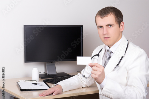 young male doctor showing visiting card in office