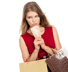 Sad thinking female shopper with shopping bags holding money