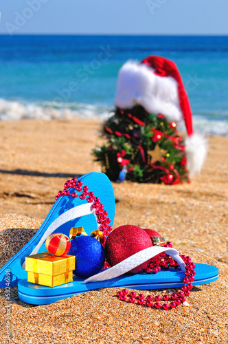 Slippers, Santa Claus hat and  new year tree on the seashore