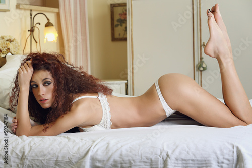 Sexy brunette woman posing on bed
