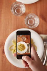 Hands taking photo of lunch with smartphone