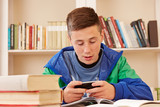 Teenager texting with smartphone while studying