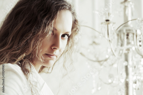 Sad beautiful woman with long curly hairs