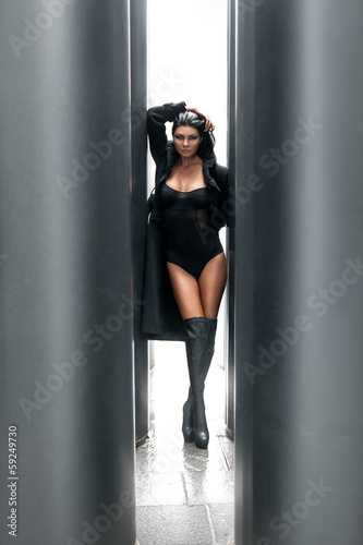 woman in lingerie posing between two black columns on street
