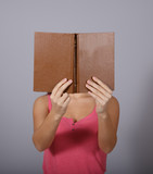 Girl covers her face with book