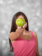 Girl with apple at light background