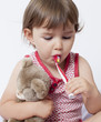 young toddler brushing her teeth with comforting teddy bear