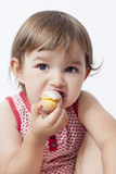 young toddler eating pastry with pleasure poster