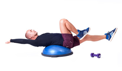 Sport man exercise with a pilates ball and dumbbells