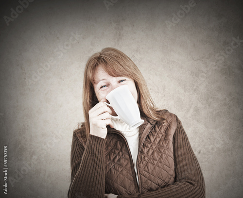 Funny woman laughing with a mug in her hand