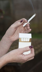 A plain cigarette packet in a woman's hand