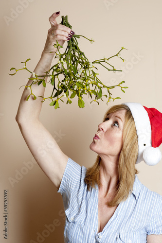 Mistletoe Woman holding a bunch of the festive decoration