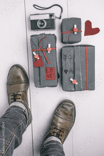 Man boots with valentines gifts box and old camera. Hipster gift