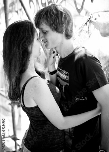 portrait of girl holding finger near boyfriends lips on street