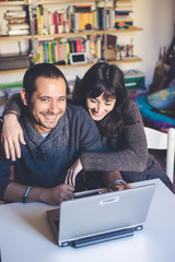 couple in love using notebook at home