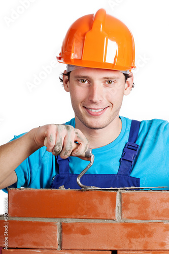 Happy handyman with trowel and brick