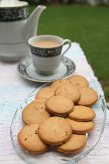 Tray full of biscuits served with tea pot and a cup
