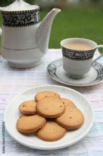 Plate full of biscuits served with tea pot and a cup