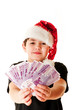 The boy in Santa's red hat holding money isolated on white