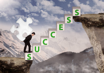 Businessman bring puzzle symbol of success at mountain