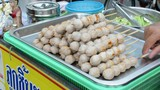 Sticks of grilled meatballs are on the tray for sale in Thailand