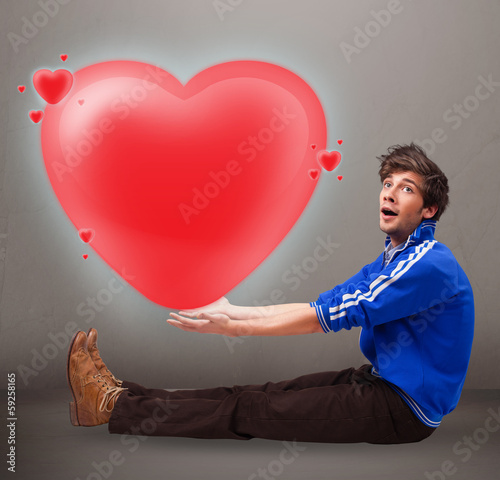 Young man holding lovely 3d red heart