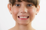 Cute cheerful little girl shows teeth