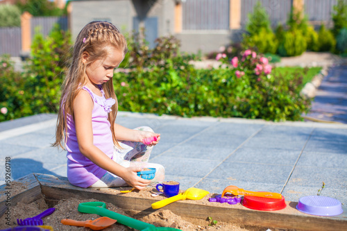 Little cute girl playing at the sandbox with toys in the yard