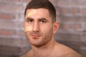 Man with plaster and bruises, after a fight