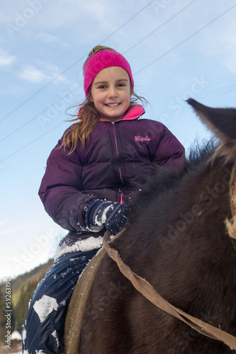Little girl riding horse in winter