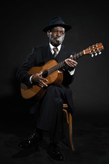 Retro senior afro american blues man. Wearing striped suit with