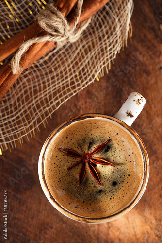 A cup of spiced coffee with anis star and cinamon sticks