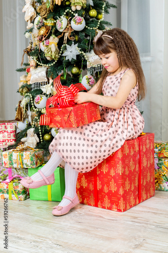 Happy little girl with christmas present smiling