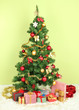 Decorated Christmas tree with gifts on green wall background